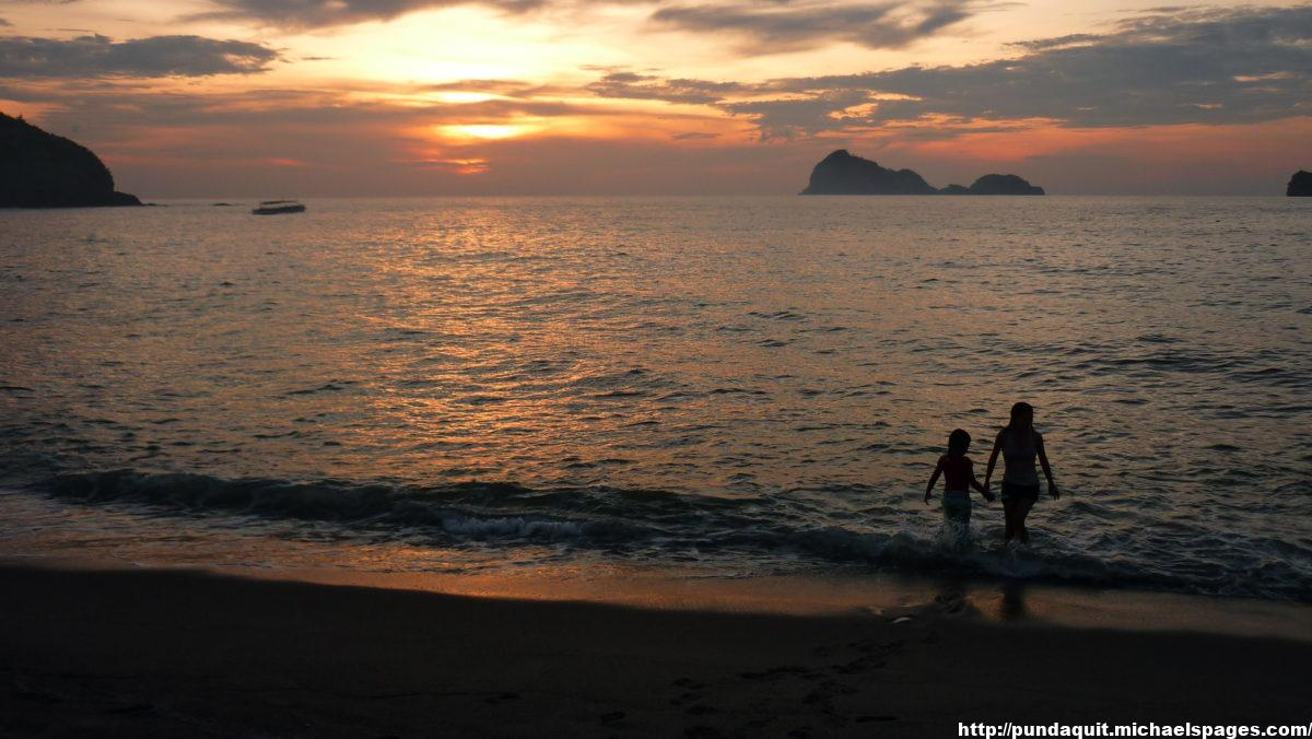 waters of the beach of Pundaquit with visible Capones Island during sunset